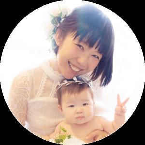 おかっぱミユキと赤ちゃんの写真。白い洋服を着て微笑んでいる。