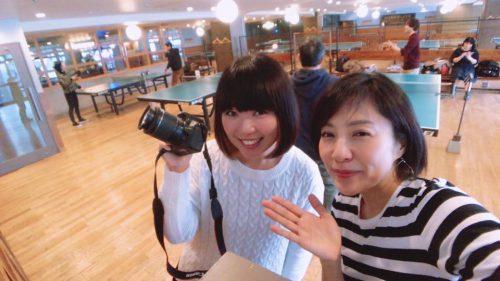 一眼レフカメラを持っているおかっぱミユキと、ボーダー柄のTシャツを着ている建部和美さん
