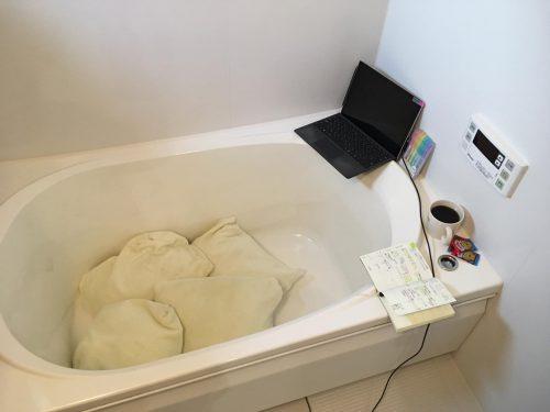 お風呂場のバスタブにパソコンやスマートフォンを持ち込んで作業スペースにしている様子